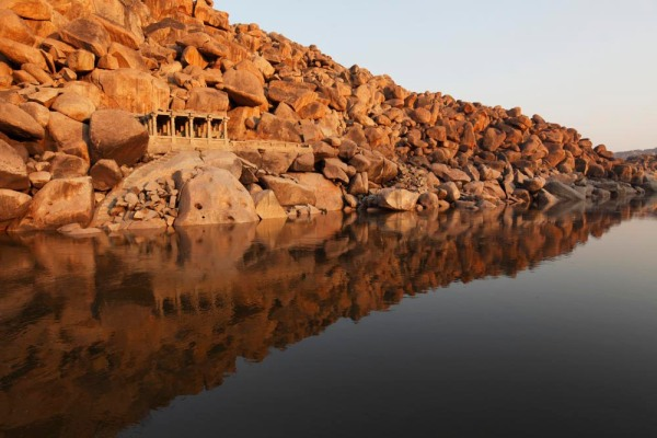 A temple built on a rocky hill that falls in to the Tungabhadra River at dawn.